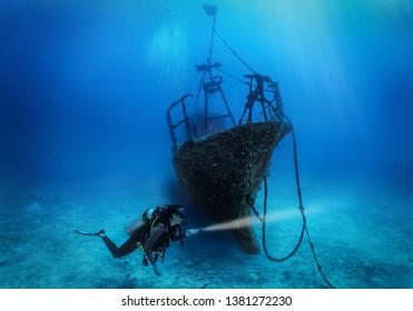 A female scuba diver explores a sunken shipwreck in the deep, blue sea