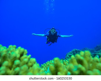 Female Scuba Diver exploring coral reef underwater with open arms