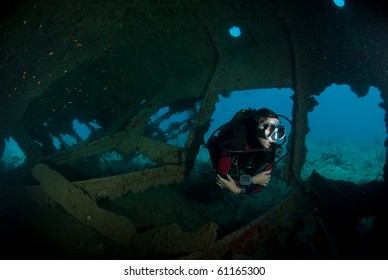 A female scuba diver exploring the inside of the SS Dunraven shipwreck. Beacon rock, Ras Mohammed national Park, Red Sea, Egypt.