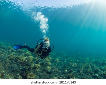 Female Scuba diver hovering over a coral reef at Tulamben, Bali Indonesia