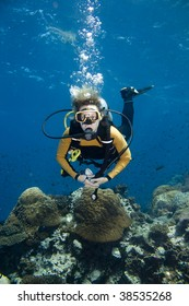 Female scuba diver over a beautiful coral reef