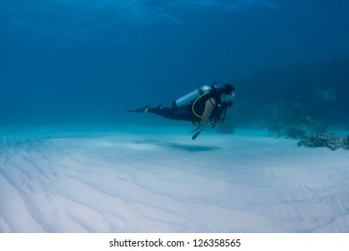 Female scuba diver over a coral reef in the Bahamas