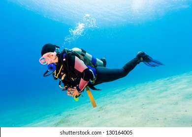 Female SCUBA diver over sand in shallow water