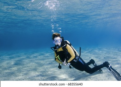 Female scuba diver over white sand in clear blue water