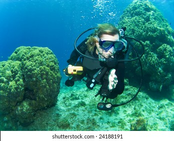 Female Scuba Diver Swimming between the Reef in Cayman Brac