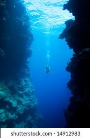 a female scuba diver, swimming into a large underwater cavern