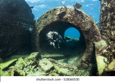 Female Scuba Diver Swimming Through a Ship Wreck