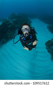 Female SCUBA Diver swims towards camera