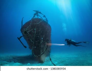 Female scuba diver with a torch explores a sunken shipwreck at the Maldives islands