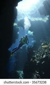 a female scuba diver in an underwater cave with sunbeams shining through the water