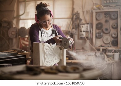 Female sculptor cutting a white marble piece with a power tool, craftswoman shaping a sculpture with an angle grinder, caucasian woman working inside an arts workshop