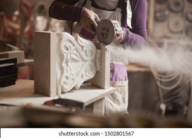 Female sculptor cutting a white marble piece with a power tool, craftswoman shaping a sculpture with an angle grinder, caucasian woman working inside an arts workshop, detail closeup of hands