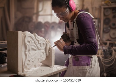 Female sculptor working on a piece using hammer and chisel, sculpting a white marble stone into a beautiful pedestal, stonemasonry and stonecraft