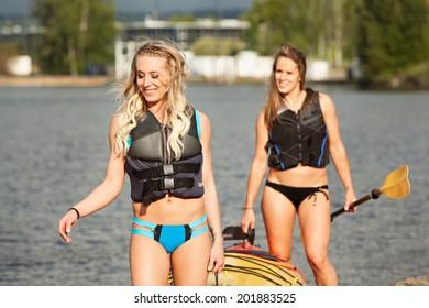 Female Sea Kayakers carrying boat