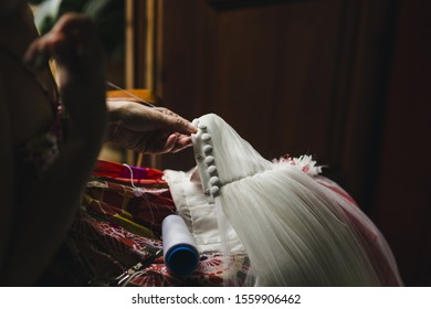 Female seamstress patching a wedding dress with thread and needles in a handmade way at home.