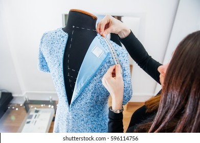 Female seamstress prepares dress to the fitting and takes measurements. Selective focus