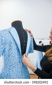 Female seamstress prepares dress to the fitting. Selective focus