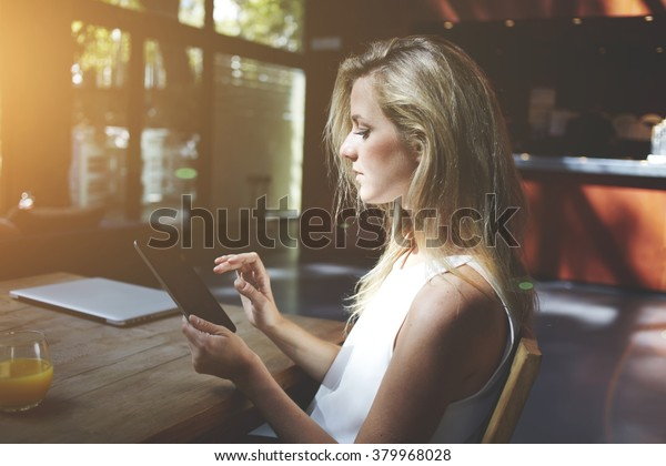 Female searching necessary information in network via touch pad while sitting at the table with closed net-book in co-working cafe, young woman chatting with friends on touch pad while relaxing in bar