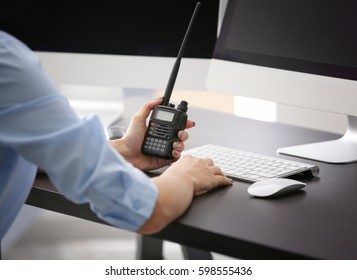 Female security guard holding portable radio in hand at workplace