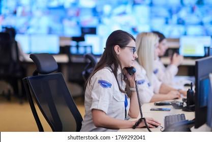 Bedienungspersonal für weibliche Sicherheitswachen, der telefonisch während der Arbeit am Arbeitsplatz mit mehreren Bildschirmen arbeitet Sicherheitsmänner, die auf mehreren Monitoren arbeiten