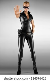 Female security guard in tight, black, sexy outfit with pistol.