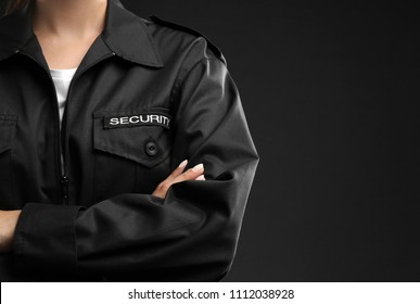 Female security guard in uniform on dark background, closeup