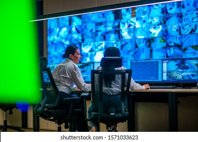 Female security guards working in surveillance room, monitoring cctv and discussing.