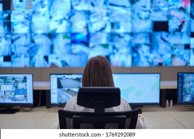 Female security operator working in a data system control room offices Technical Operator Working at  workstation with multiple displays, security guard working on multiple monitors