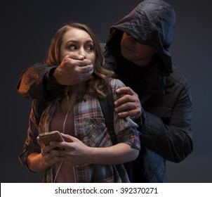 FEMALE SELF DEFENSE SERIES- Medium studio shot of a Teenage Girl on a cell phone.  A scary stranger has grabbed her from behind and you can see his teeth.