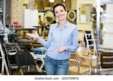 Female seller demonstrates an assortment of interior items in the store