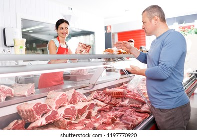 Female seller helping male customer choosing different meat in butcher's shop