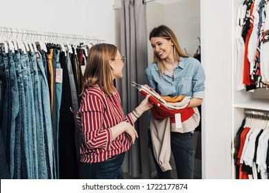 Female seller helps buyer to choose between diferent clothes.
