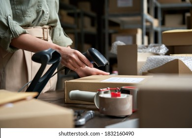 Female seller online store worker holding scanner scanning parcel bar code packing e commerce post shipping box preparing online retail shop order in dropshipping delivery service warehouse.