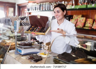 Female seller showing box of chocolate candies in confectionery store