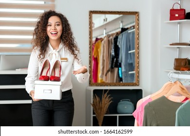 Female seller with stylish shoes in modern clothes store