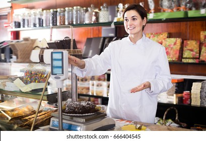 Female seller weighing festive chocolate cake in confectionery