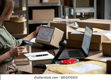 Female seller worker online store holding scanner scanning parcel barcode tag packing ecommerce post shipping box checking online retail store orders in dropshipping delivery service warehouse.