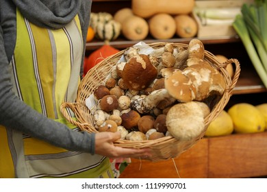 female selling fench cepe (boletus) in retail store