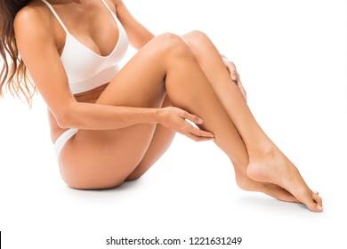 Female semi naked model with soft skin sitting against white background