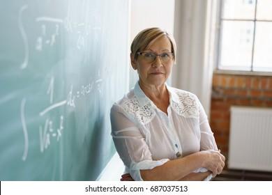 Female senior teacher standing by blackboard in classroom