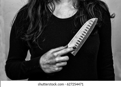 Female serial killer holding a knife in his hand