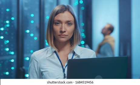 Female server technician doing checkup operations on laptop computer coworking in cyber server room. Portrait of professional woman engineer in data center interior.