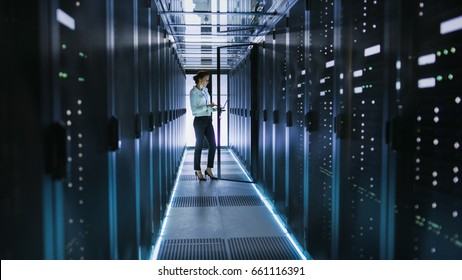 Female Server Technician Stands next to Cabinet in Data Center Corridor with Rows of Rack Servers. She's Running Diagnostics on Her Computer