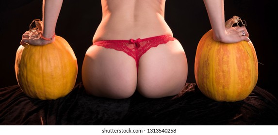Female with sexy ass posing with two pumpkins in studio