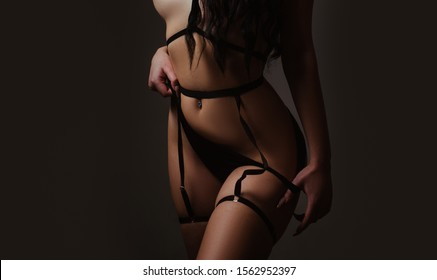 Female in sexy bikini. Sexy lingerie. Bondage and bdsm concept. Confident lover. Seductive temptress. Slim woman dressed in black lingerie and tied with ropes. Lingerie sexy girl model in darkness.