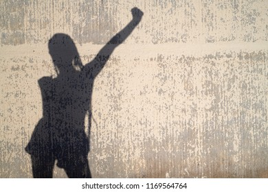 Female shadow silhouette on concrete wall in sunlight with raised hand