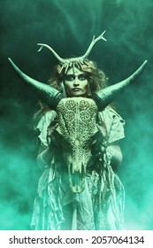 Female shaman in an ethnic dress doing a mysterious ritual with a help of an animal skull. Dark mystical background with green haze. Black magic concept, fantasy. Paganism. Halloween.