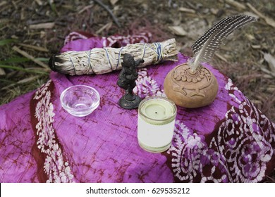 Female shaman lighting candle at altar seated on the ground. The symbols represent fire, water, air and earth with candle flame, sage, water in small dish, dancing Ganesha, rattle with bird feather.,