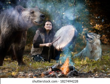 Female shaman playing her shaman sacred drum in the forest among wild animals - a dog and a bear. The theme of totem animals in shamanism