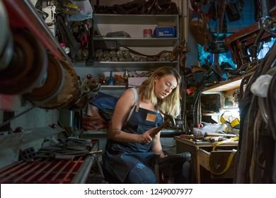 Female shoemaker in workshop. Shoemakers working in a workshop. Shoemaker sanding shoe lasts in a workshop. Woman shoemaker repairing shoes